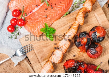 Grilled salmon on skewer with tomatoes and red pepper - stock photo