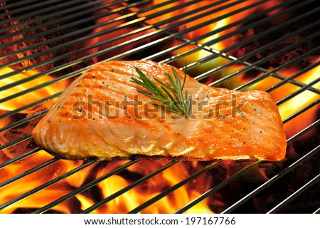 Grilled salmon on the flaming grill. - stock photo