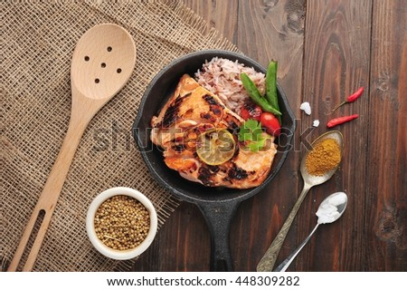 Grilled salmon,rice and vegetables iron pan with ingredients on rustic background. - stock photo
