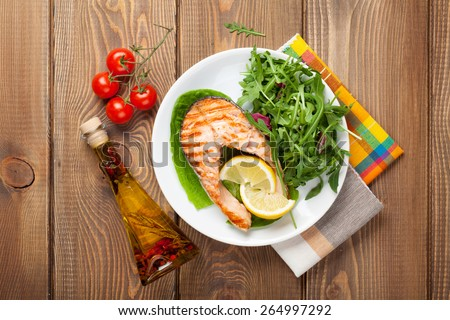 Grilled salmon, salad and condiments on wooden table. Top view - stock photo