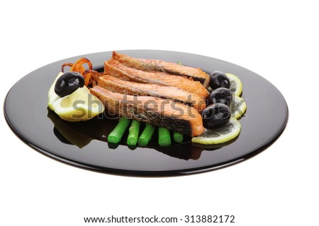 grilled salmon slices with asparagus lemon and olives on black plate isolated over white background - stock photo