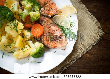 Grilled salmon steak garnished with vegetables. Closeup. - stock photo