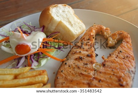 Grilled Salmon steak serve with salad and potato fried - stock photo