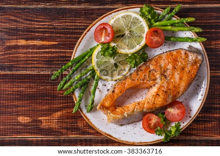 Grilled salmon steak served with asparagus, tomato and lemon on dark wooden background. - stock photo