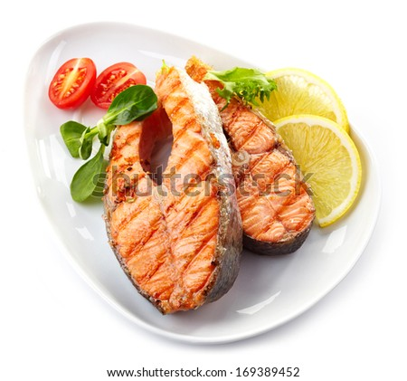 grilled salmon steak slices on a white plate - stock photo