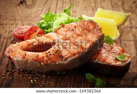 grilled salmon steak slices on wooden cutting board - stock photo