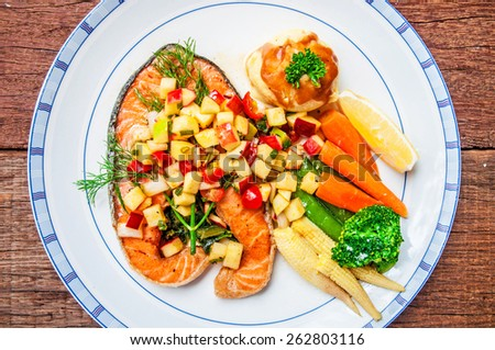 Grilled Salmon Steak with Apple Salsa Sauce, serving side with Spinach, Mash Potato, Lemon, Butter Vegetable. Concept and Idea of Fusion Food, Cooking Style. / on wood table Background. Top view. - stock photo