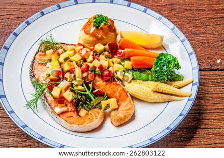 Grilled Salmon Steak with Apple Salsa Sauce, serving side with Spinach, Mash Potato, Lemon, Butter Vegetable. Concept and Idea of Fusion Food, Cooking Style. / on wood table Background. - stock photo