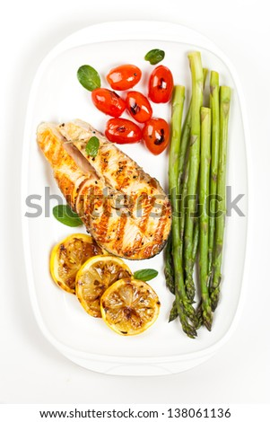 Grilled salmon steak with asparagus and cherry tomatoes - stock photo