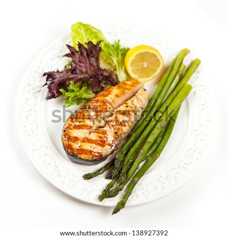 Grilled salmon steak with asparagus, lemon and salad - stock photo