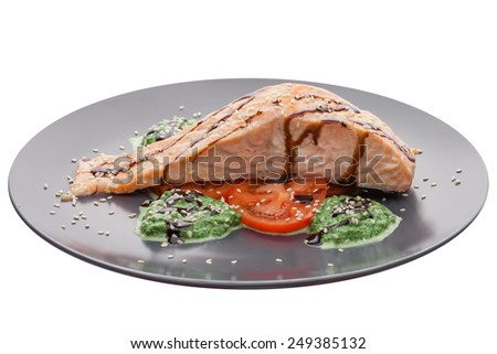 Grilled salmon steak with tomatoes isolated on white background. Clipping path