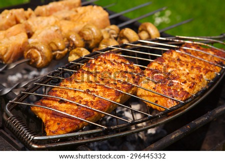 Grilled salmon steaks on the grill.Portobello mushrooms marinated and grilling close up.