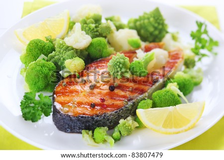 grilled salmon with broccoli and cauliflower on white plate - stock photo