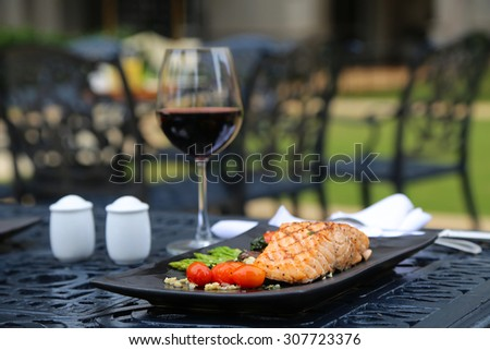 Grilled Salmon with Cherry Tomatoes and a Glass of Red Wine atop Ornamented Black Metal Table with Blurred Chairs in the Background