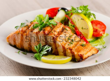 Grilled Salmon with fresh salad and lemon. Selective focus - stock photo