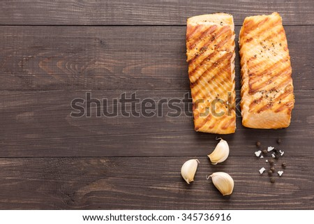 Grilled salmon with garlic, pepper, salt on wooden background. - stock photo