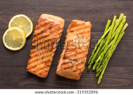 Grilled salmon with lemon, asparagus on the wooden background. - stock photo