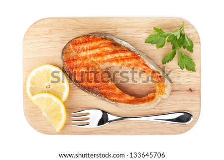 Grilled salmon with lemon slices and parsley on cutting board. Isolated on white background - stock photo