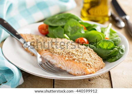 Grilled salmon with nut crust served with spinach and tomato - stock photo