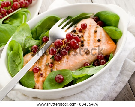 grilled salmon with redcurrants and fresh spinach - stock photo