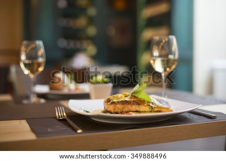 Grilled salmon with sauce and herbs served at restaurant - stock photo