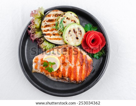 Grilled salmon  with sliced zucchini and courgette, lettuce and lemon