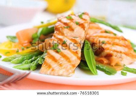 grilled salmon with spring vegetables on white plate, soft focus - stock photo