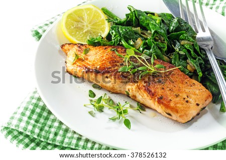 grilled salmon with thyme, lemon and spinach on a plate, vegetarian low carb dish, green white napkin on a white background, selected focus, narrow depth of field - stock photo