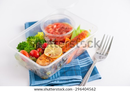 Grilled salmon with tomato salsa and salad cooked by clean food concept in lunch box - stock photo
