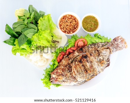 Grilled salted tilapia fish on white dish