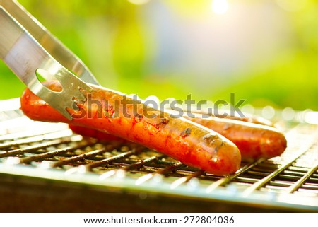 Grilled Sausage on the flaming Grill. BBQ. Bearbeque outdoors. Barbecue - stock photo