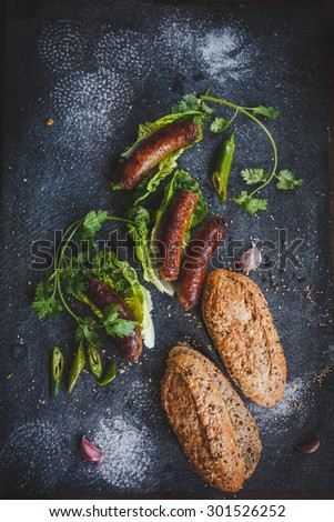 Grilled sausage with green salad , pepper and sandwich wholegrain baguette. Homemade concept from preparing sandwich. Rustic dark image from above. - stock photo