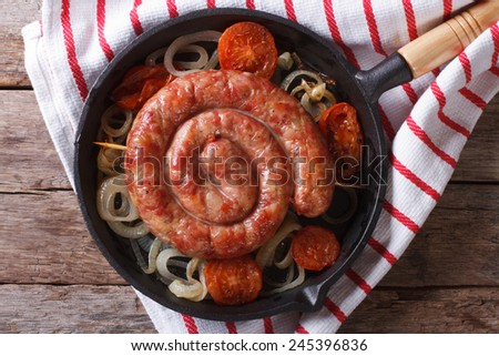 Grilled sausage with onions and tomatoes in a pan. horizontal view from above close-up  - stock photo