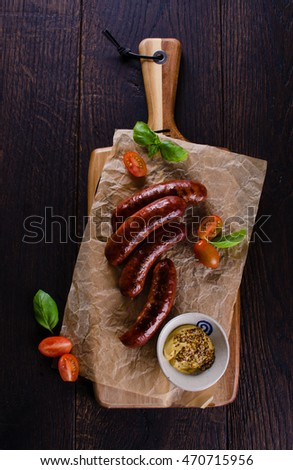 Grilled sausages on cutting board on wooden background