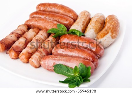 Grilled sausages on white plate - stock photo