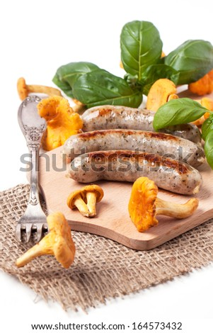 Grilled sausages with chanterelle and basil, server on wooden cutting board with fork and sacking cloth over white - stock photo