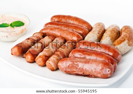 Grilled sausages with sauce on white plate - stock photo