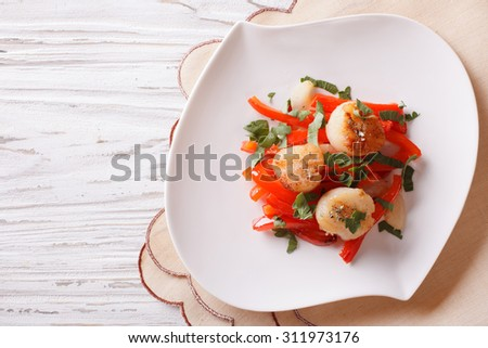 Grilled Scallops with peppers and herbs on a plate. horizontal view from above