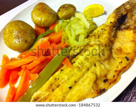Grilled sea bass with potatoes and stewed vegetables - stock photo