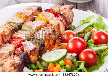 Grilled shashlik with vegetables on plate