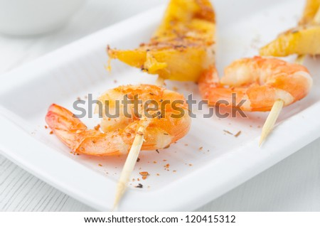 grilled shrimp and mango in the glaze closeup on white dish