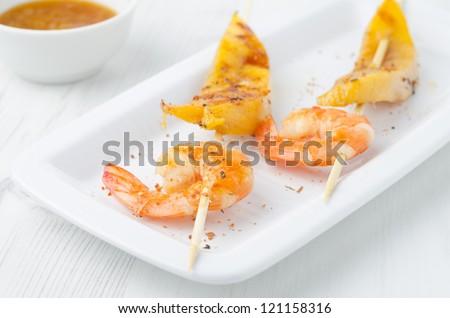 grilled shrimp and mango in the glaze on white dish, horizontal - stock photo