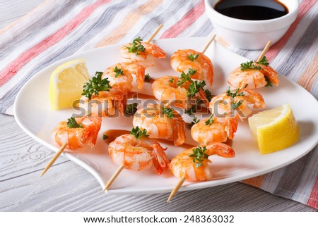 Grilled shrimp on skewers with lemon and sauce on the table close-up. horizontal  - stock photo