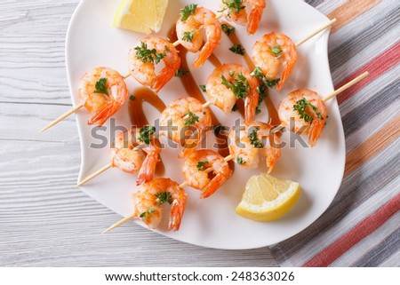 Grilled shrimp on skewers with lemon on a plate close-up. horizontal view from above  - stock photo