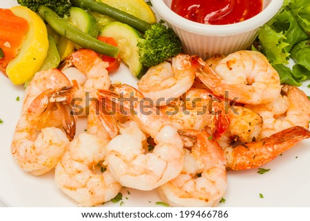Grilled shrimp served with vegetable medley and hush puppies. - stock photo