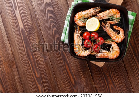Grilled shrimps on frying pan on wooden table. Top view with copy space - stock photo
