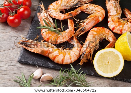 Grilled shrimps on stone plate over wooden table - stock photo