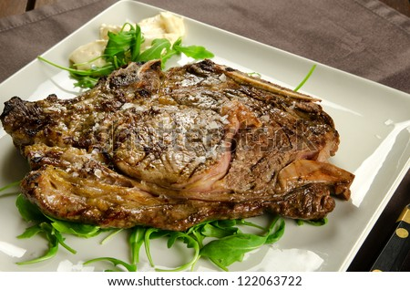 Grilled sirloin beef steak on white plate, BBQ meat - stock photo