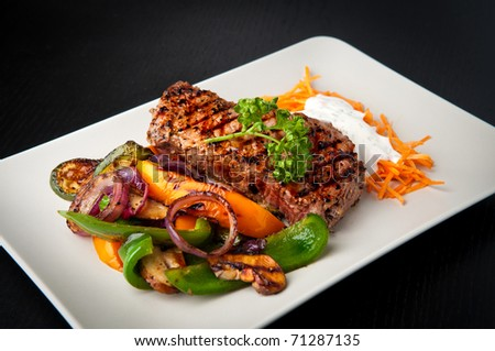 Grilled sirloin steak with grilled vegetables and carrot salad - stock photo