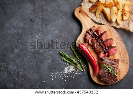 Grilled sliced beef steak on cutting board over stone table. Top view with copy space - stock photo